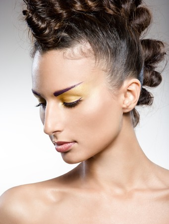 studio portrait of young beautiful brunette with creative makeup and hairstyle photo