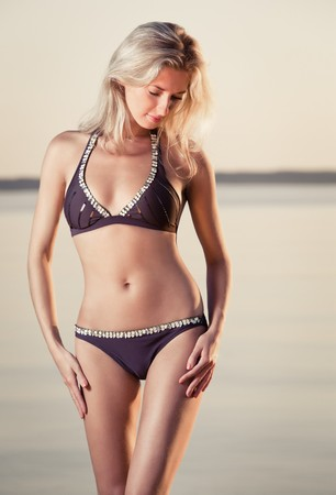 young gorgeous caucasian blonde posing at sunset on the beach photo
