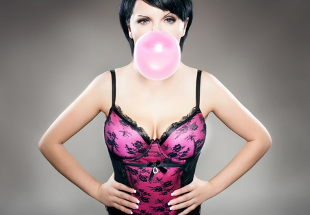 sexy brunette in pink lingerie playing with bubble gum Stock Photo - 8224804