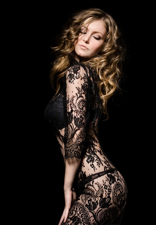 sensuality: gorgeous young model in lace dress dancing, over black