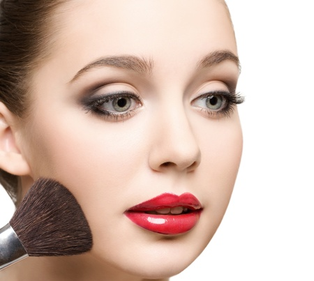 face powder: close-up portrait of young beautiful caucasian woman applying  powder to her cheeks