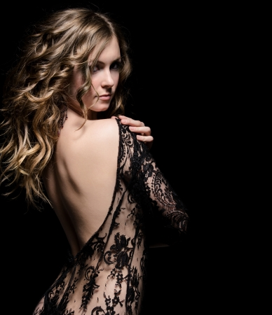 sensuality: young gorgeous lady posing in lace dress, over black. space for copy
