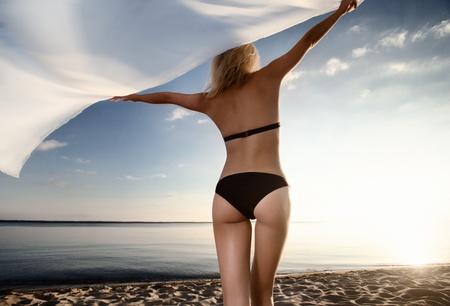jonge gorgeous Kaukasische blonde model poseren bij zonsondergang op het strand