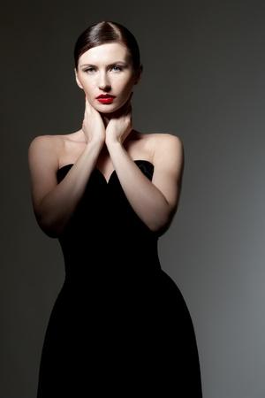 classy woman: young caucasian woman in back dress posing, studio shot  Stock Photo