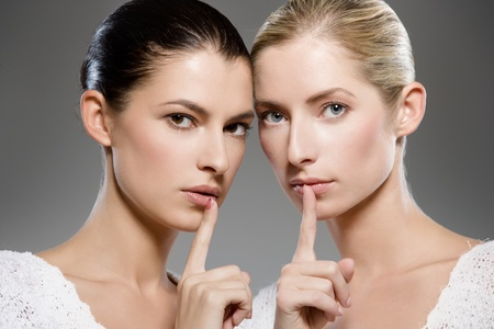 two young caucasian women gesturing shh - keep it secret photo