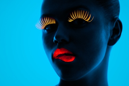 ultraviolet: close-up portrait of young woman wearing UV lashes and lipstick under blacklight