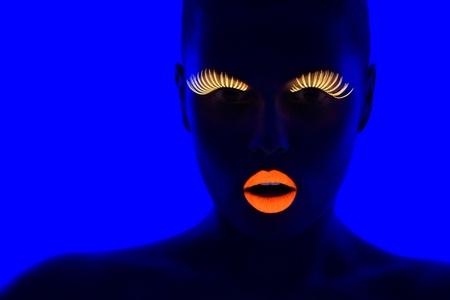 블랙 라이트 아래 UV 속눈썹, 립스틱을 착용하는 젊은 여자의 클로즈 업 초상화