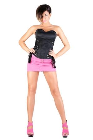 minijupe: jeune mannequin en mini jupe rose et corset noir posant, isolé sur blanc Banque d'images
