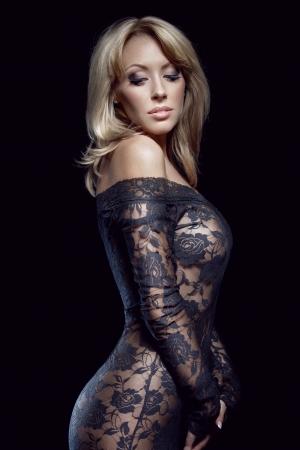 prachtige blonde in kanten jurk, geïsoleerd op zwart, studio-opname