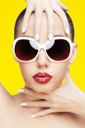 노란색 배경 위에 선글라스를 착용하는 화려한 젊은 백인 여자의 근접 촬영 초상화,