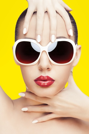 fashionable sunglasses: closeup portrait of young gorgeous caucasian woman wearing sunglasses, over yellow background Stock Photo