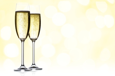 champagne flutes: two glasses of sparkling wine with copyspace and abstract lights background