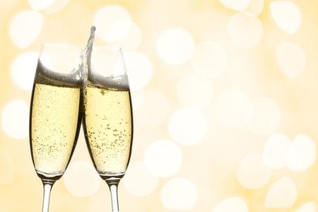 saúde: dois copos de vinho espumante com copyspace e luzes abstratas fundo Banco de Imagens