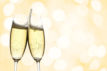 cheers: two glasses of sparkling wine with copyspace and abstract lights background