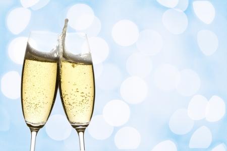 brindis champan: dos vasos de vino espumoso con luces abstractas, sobre fondo azul