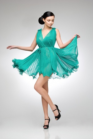 dress blowing in the wind: brunette in teal dress