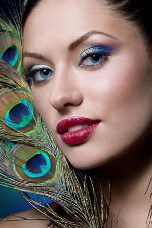 plumas de pavo real: joven morena con el maquillaje creativo
