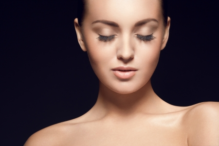 gorgeous model  with eyes closed, over black background, studio shot Standard-Bild