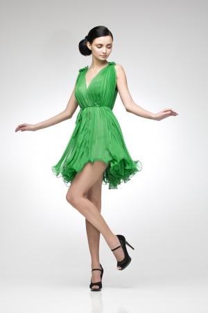 belles jambes: brunette élégante robe verte posant dans le studio