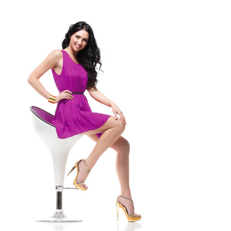 young gorgeous caucasian brunette in violet dress on the chair, isolated on white, studio shot