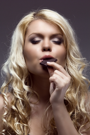 young caucasian blonde eating chocolate, with her eyes closed photo