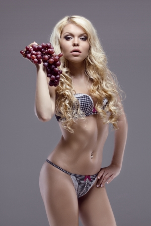 young slim model in sexy lingerie posing with grape, studio shot photo
