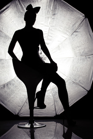 sexy woman posing in front of giant reflector, silhouette shot photo