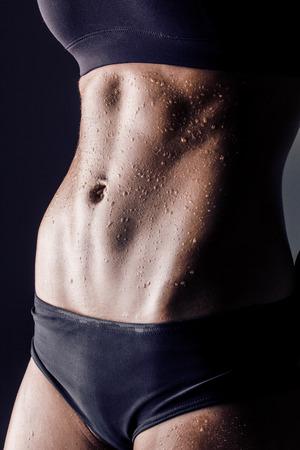 closeup girato in studio del corpo femminile allenato, modello di fitness abs