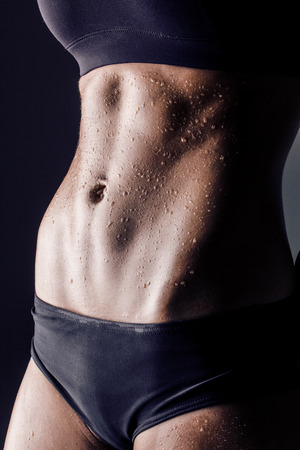 sweat girl: closeup studio shot of trained female body, fitness model abs Stock Photo
