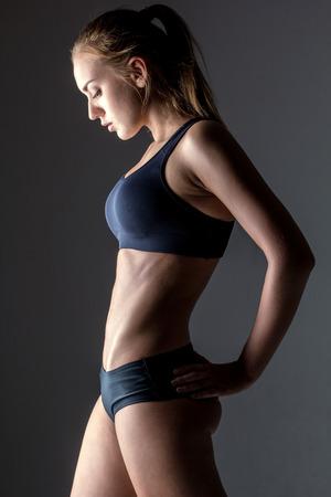 atletisch: profiel van aantrekkelijke fitness vrouw, opgeleid vrouwelijk lichaam, lifestyle portret, Kaukasisch model Stockfoto