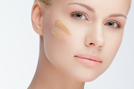 close-up portrait of young beautiful woman with cosmetic foundation