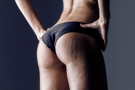 closeup of  young female athlete back, trained buttocks, fit shape photo