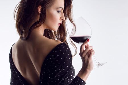 bebiendo vino: joven hermosa morena con un vaso de vino tinto