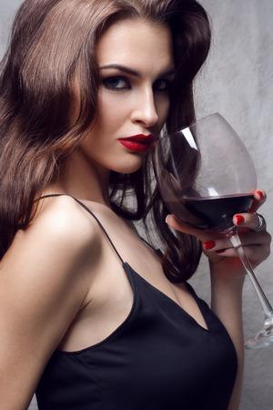 jovenes tomando alcohol: joven hermosa morena con un vaso de vino tinto