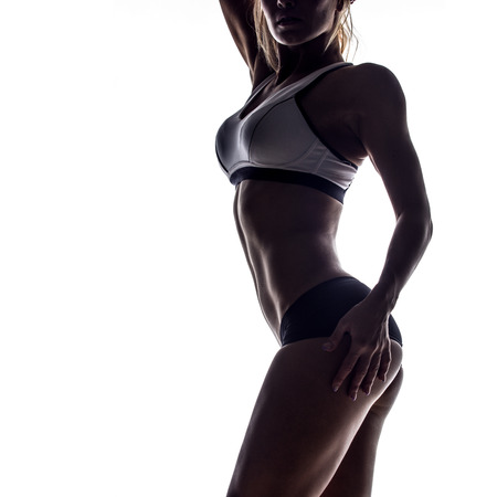 slim tummy: silhouette of attractive fitness woman, trained female body, lifestyle portrait, caucasian model Stock Photo