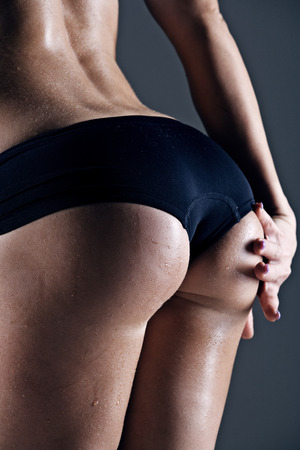 woman buttocks: closeup of  young female athlete back, trained buttocks, fit shape