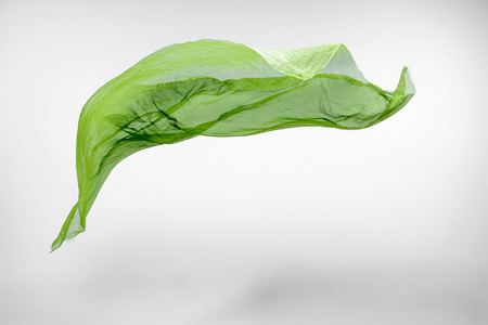 signe de la main: piece of green fabric flying, high speed studio shot, design element Banque d'images