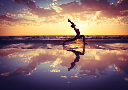 silhouet van de vrouw het beoefenen van yoga op het strand bij zonsondergang