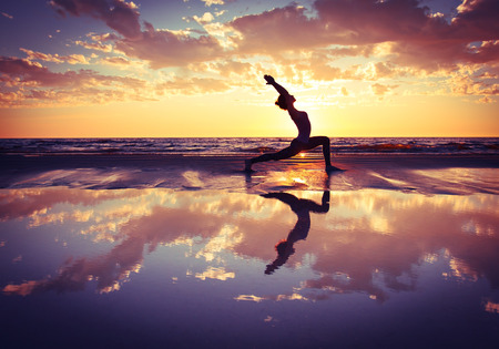 harmony: silhouette of woman practicing yoga on the beach at sunset