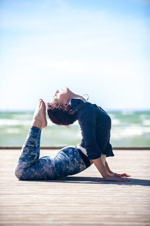 Caucasian woman: woman practicing yoga on the coast of sea, sunny day