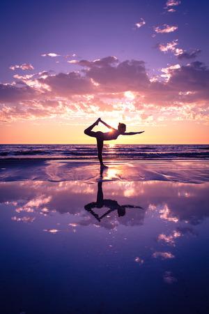 corpo umano: sagoma di donna praticare yoga sulla spiaggia al tramonto