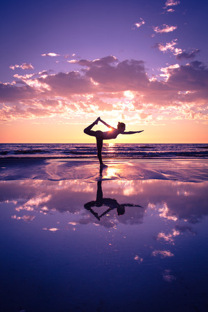 human body: silhouette of woman practicing yoga on the beach at sunset