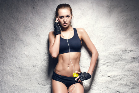 girl in sportswear: attractive fitness woman with mp3 player, caucasian brunette model