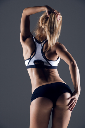 girl fitness: young female athlete back, trained buttocks, fit shape