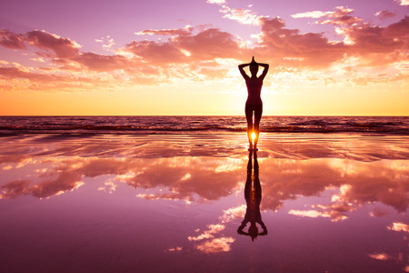 yoga girl: silhouette of woman practicing yoga on the beach at sunset