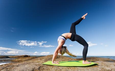若い白人フィットネス女性海岸でヨガの練習