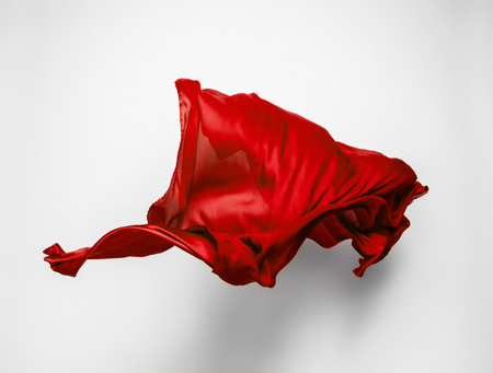 dynamic movement: piece of red fabric soaring, art object, design element Stock Photo