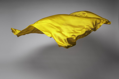 dynamic movement: yellow flying fabric - art object, design element
