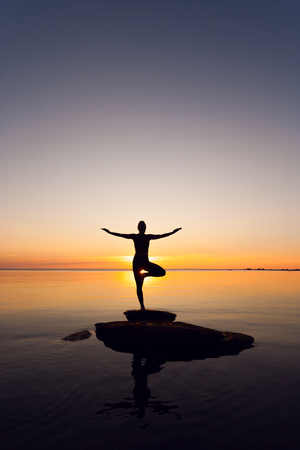 caucasian fitness woman practicing yoga on the beach at sunset Stock Photo