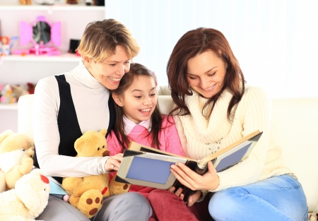 Grandmother, mother, and daughter reading a book together photo